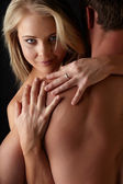 Young and fit caucasian adult couple in an embrace. Semi-nude and topless against a dark background . — Stock Photo