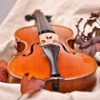 Details of a violin and autumn leaves on brown background — Stock Photo