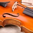 Fragment of violin isolated on beige background - Stock Photo