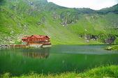 Casa de madera marrón en lago glaciar con agua muy clara de la montaña, balea lac, Rumania — Foto de Stock