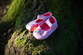 Pink baby shoes in a green natural environment — Stock Photo