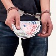 Man in handcuffs is holding money over white background — Stock Photo