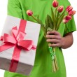 Gift box and fresh tulips in man's hand — Stock Photo #23977457