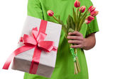 Gift box and fresh tulips in man's hand — Stock Photo