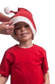 Happy boy is helped by his mother to put his Santa hat — Stock Photo