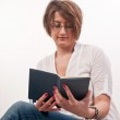 Close up of young woman with glasses sitting on chair and readin — Stock Photo #24951887