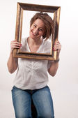 Funny beautiful woman holding around her face a frame — Stock Photo