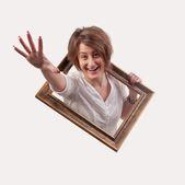 Divertido hermosa mujer que sale de un marco vacío — Foto de Stock