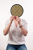 Young woman with dartboard in front of face, Bull's Eye — Stock Photo