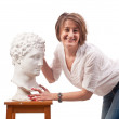 Beautiful woman standing near antique man statue and touches his — Stock Photo #25102093