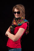 Fashion woman with sunglasses and scarf posing on black backgrou — Stock Photo