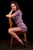 Sensuale bruna seduta e in posa su una sedia contro un nero b — Foto Stock