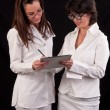 Stock Photo: Two female doctors discussing together on medical exam