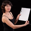 Studio shot of young woman writing notes on clipboard and showin — Stock Photo