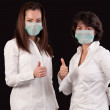 Friendly female doctors with thumbs up over black — Stock Photo
