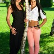 Full length portrait of two girlfriends posing next to a tree in — Stock Photo