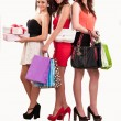 Group of three happy young women out of shopping with colored ba — Stok fotoğraf