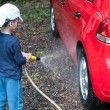 Little boy playing with water hose, wash car — Stock Photo