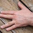Man hand sign on wooden background — Stock Photo