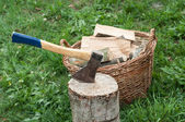 An axe stuck in a log in front of basket with logs fire — Stock Photo