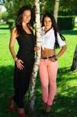 Retrato de longitud completa de dos amigas posando junto a un árbol en — Foto de Stock