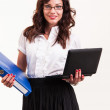 Beautiful woman with glasses holding laptop and binder — Stock Photo