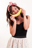 Young woman holds up a banana to her mouth, imitating a smile on — Stock Photo