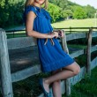 Young pretty blonde posing in summer field near a fence — Foto Stock