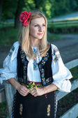 Beautiful singer with flowers posing in traditional costume, rom — Stock Photo
