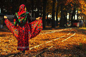 Romantic young gypsy woman pulls up dress and walks on the railr — Stock Photo