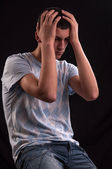 Upset teenager with head in hands wincing from stress, anguish o — Stock Photo