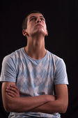 Serious and thoughtful teen boy with hands cross sits on chair — Stock Photo