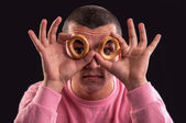 Cheerful teenager look through a bagels hole — Stock Photo