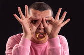 Young man with hand over eyes and a ring bagel in his mouth, loo — Stock Photo