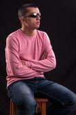 Unga kaukasiska man med solglasögon sitter på stol — Stockfoto