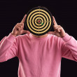 Portrait of teenager holding a dartboard over his face — Stock Photo