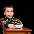 Smiling little boy plays indoor with toy car — Stock Photo