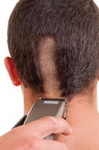 Man having a haircut with a hair clippers over a white backgroun — Stock Photo