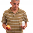 Moffering pill in one hand and apple in another. Copy space b — Stock Photo #41955101
