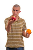 Young man comparing apples to oranges — Foto Stock