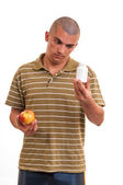 Man offering pill in one hand and apple in another. Copy space b — Foto de Stock