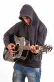Sad teenager in hoodie playing acoustic guitar. Trying to write  — Stock Photo