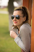 Beautiful blonde woman in the gazebo. wearing sunglasses and pos — ストック写真
