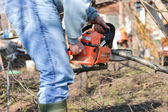 Lumberjack working with chainsaw, cutting wood. Selective focus — Stock fotografie