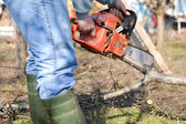 Lumberjack working with chainsaw, cutting wood. Selective focus — Foto de Stock