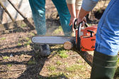 Lumberjack working with chainsaw, cutting wood. Selective focus — Стоковое фото