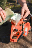 Hand refilling the chainsaw with fuel — Stock Photo