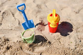 Colorful summer beach toys, bucket, sprinkler and shovel on sand — Stock Photo