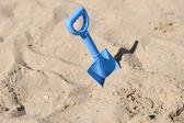 Niebieski plaża łopaty tkwi w piasku przez dziecko — Zdjęcie stockowe