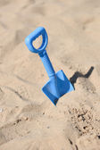 Blue beach shovel stuck in the sand by a child — Stockfoto
